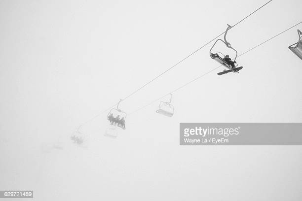 Low Angle View Of Ski Lifts Against Sky During Foggy Weather
