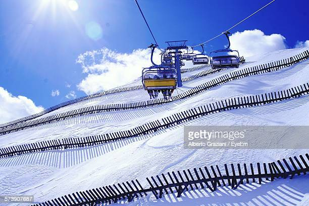 Low Angle View Of Ski Lifts Over Snow Cover Mountain Against Sky