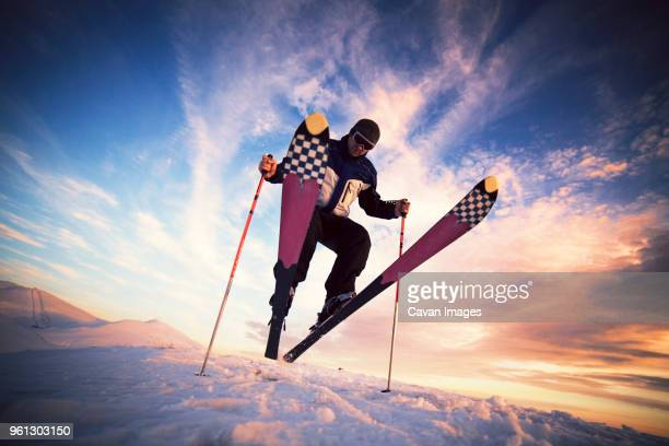 Low angle view of skier jumping on snow against sky