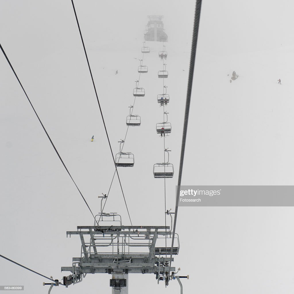 Low angle view of skiers on ski lifts : Stock Photo
