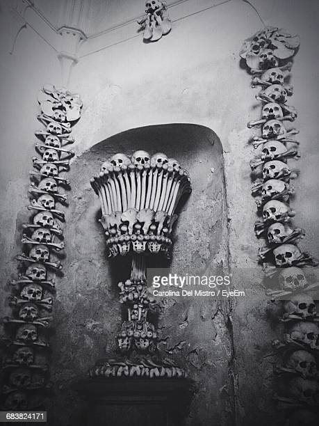 Low Angle View Of Skulls And Bones On Wall At Cemetery