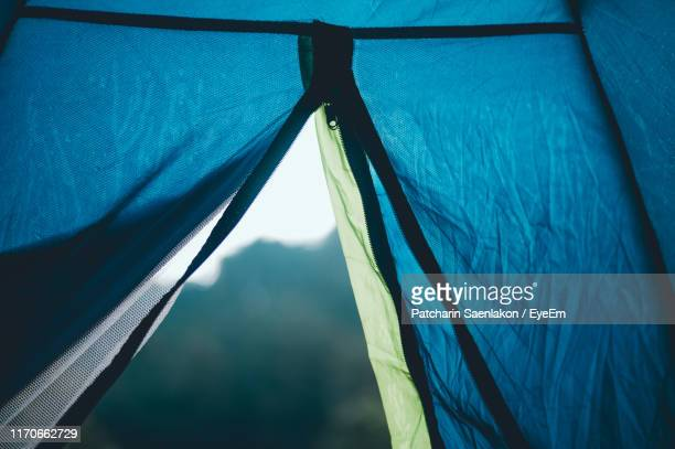 low angle view of sky seen through open zipper of tent - zipper stock pictures, royalty-free photos & images
