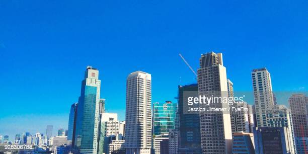 low angle view of skyscrapers against blue sky - makati stock photos and pictures
