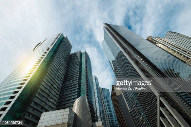 low angle view of skyscrapers against cloudy sky - makati stock photos and pictures