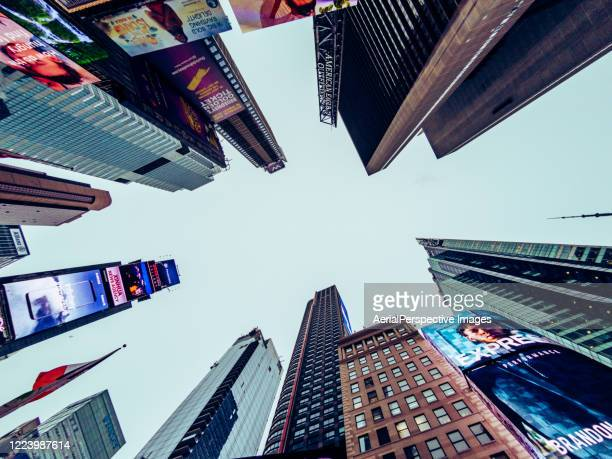 low angle view of skyscrapers in times square at dusk - times square manhattan stock pictures, royalty-free photos & images