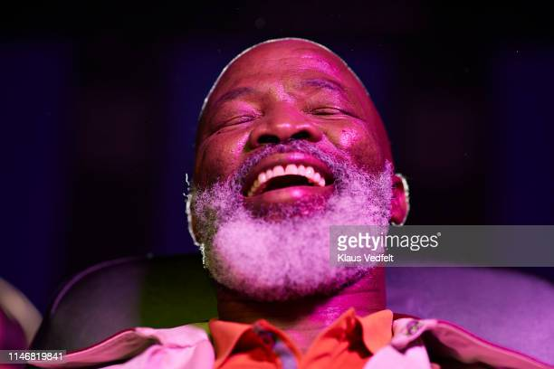 low angle view of smiling bearded mature man in movie theater - comedy film stock pictures, royalty-free photos & images