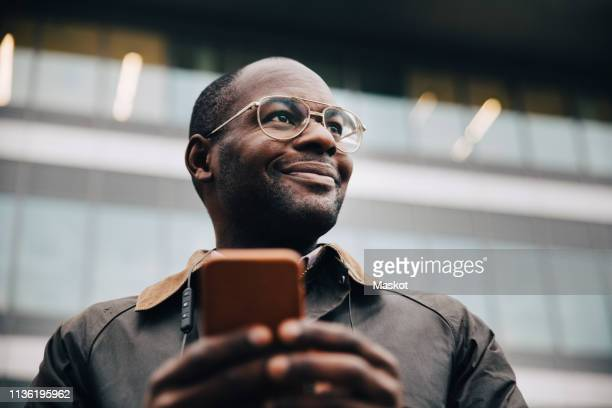 low angle view of smiling businessman using smart phone looking away while standing against building in city - looking away stock pictures, royalty-free photos & images