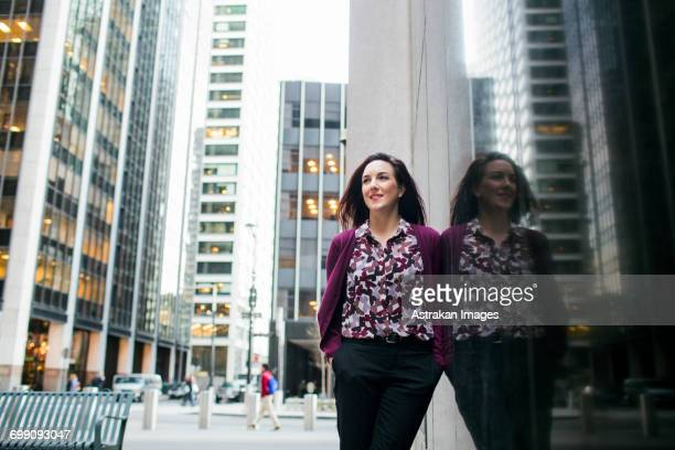 low angle view of smiling businesswoman standing by glass window in city - purple suit stock pictures, royalty-free photos & images
