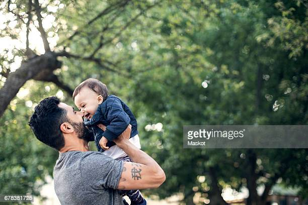 Low angle view of smiling father picking up toddler at park