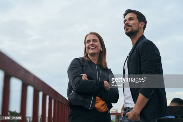 low angle view of smiling friends looking away while standing on terrace against sky - hands in pockets stock pictures, royalty-free photos & images