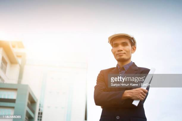 low angle view of smiling man holding paper while standing against sky - 東南アジア ストックフォトと画像