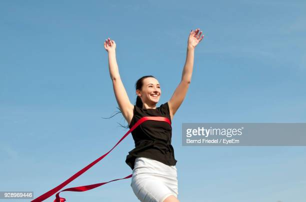 low angle view of smiling mid adult racer crossing finishing line - finish line stock pictures, royalty-free photos & images
