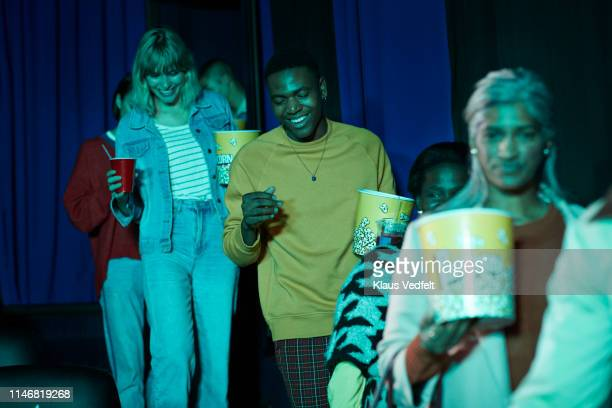 low angle view of smiling spectators walking cinema hall at movie theater - blue film video stock pictures, royalty-free photos & images