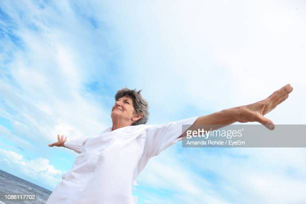 Low Angle View Of Smiling Woman With Arms Outstretched At Beach Against Sky