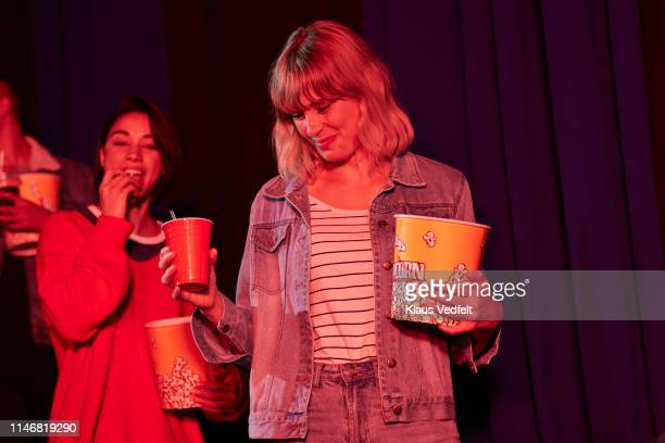 low angle view of smiling young female friends with snacks and soda entering cinema hall in movie theater - industria cinematográfica fotografías e imágenes de stock