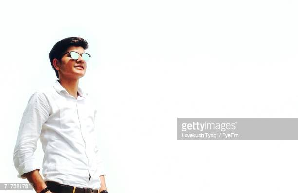 Low Angle View Of Smiling Young Man Standing Against Clear White Sky