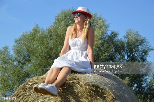Low Angle View Of Smiling Young Woman Sitting Hay Bale