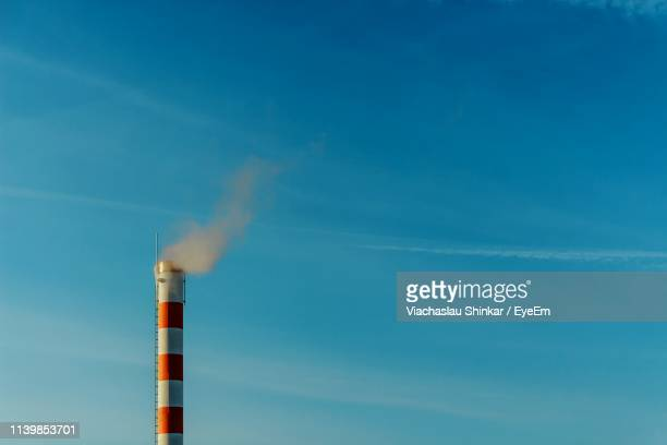 low angle view of smoke emitting from chimney against blue sky - smog stock pictures, royalty-free photos & images