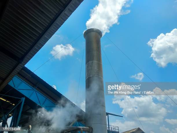 low angle view of smoke emitting from factory against sky - 煙突 ストックフォトと画像