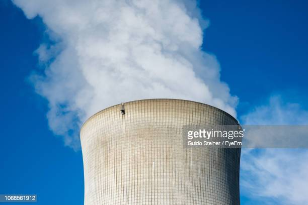 low angle view of smoke stack against sky - cooling tower stock pictures, royalty-free photos & images