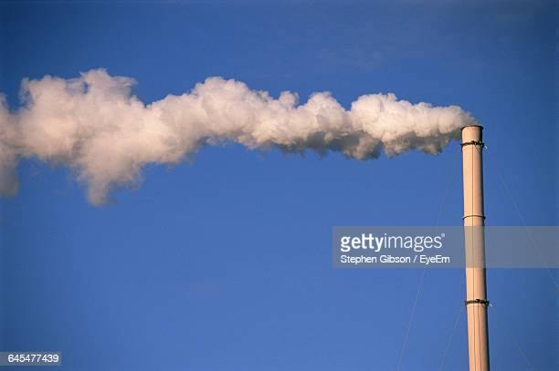 Low Angle View Of Smoke Stack Emitting Smoke In Clear Blue Sky