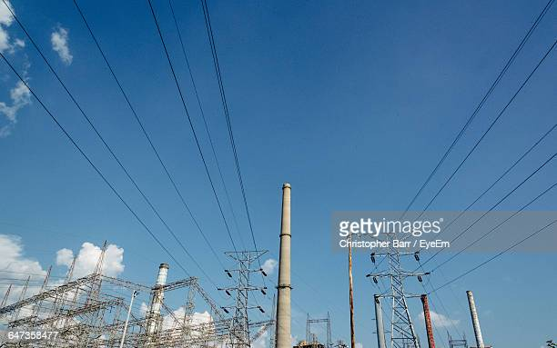 low angle view of smoke stacks and electricity pylons against sky - barr stock pictures, royalty-free photos & images