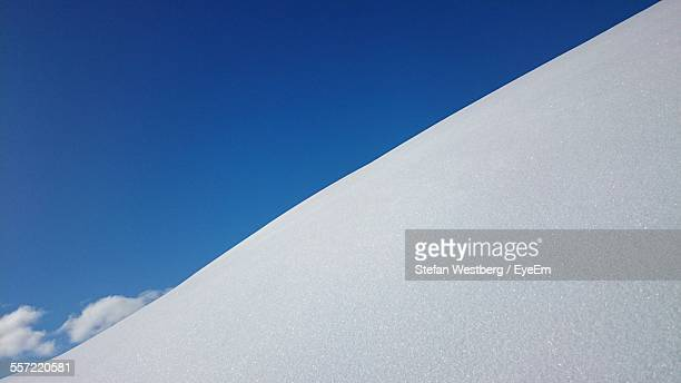 Low Angle View Of Snow Covered Hill Against Blue Sky