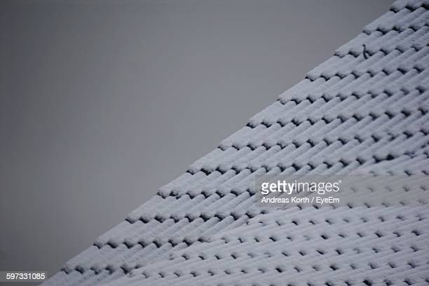 Low Angle View Of Snow Covered House Roof Against Sky