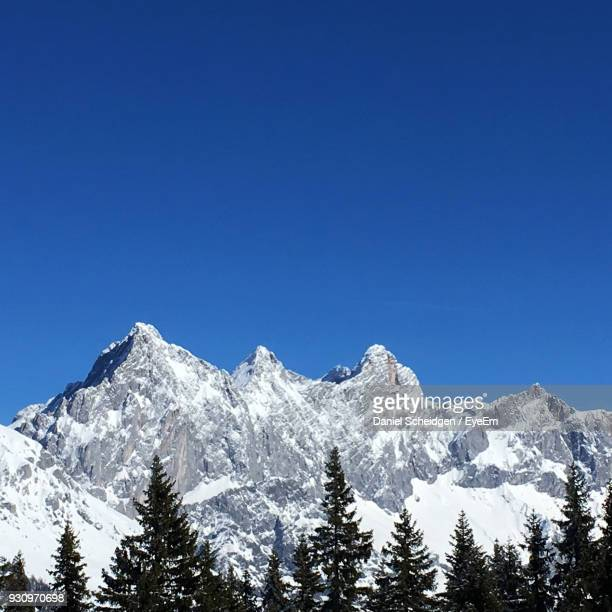 Low Angle View Of Snow Mountains Against Clear Blue Sky