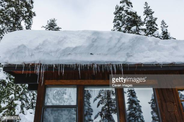 low angle view of snow on house roof with icicles - deep snow stock pictures, royalty-free photos & images