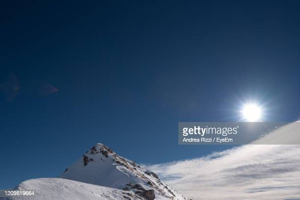 low angle view of snowcapped mountain against blue sky - andrea rizzi fotografías e imágenes de stock