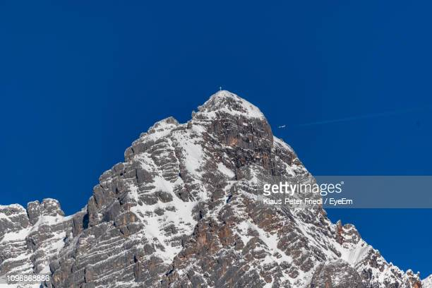 low angle view of snowcapped mountain against clear blue sky - saalfelden stock pictures, royalty-free photos & images