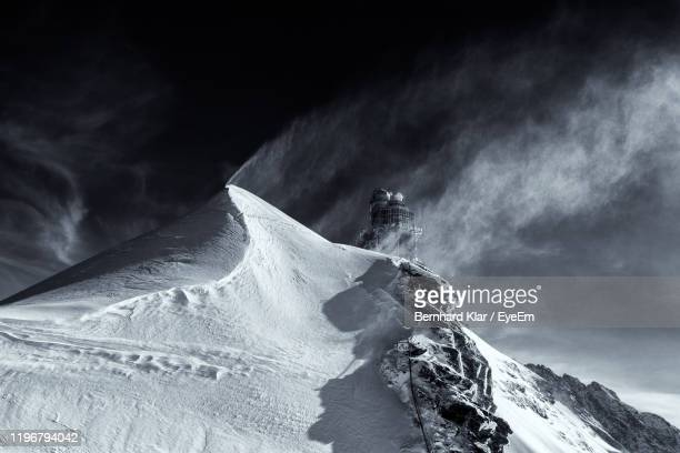 low angle view of snowcapped mountain against sky - snowcapped mountain stock pictures, royalty-free photos & images