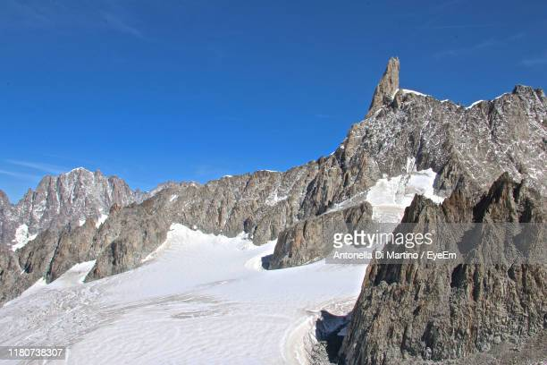 low angle view of snowcapped mountains against clear blue sky - antonella di martino foto e immagini stock
