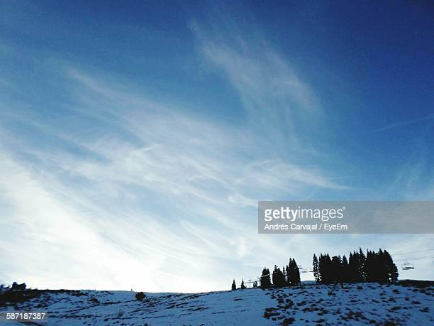 low angle view of snowcapped mountains against cloudy blue sky during winter - carvajal stock photos and pictures