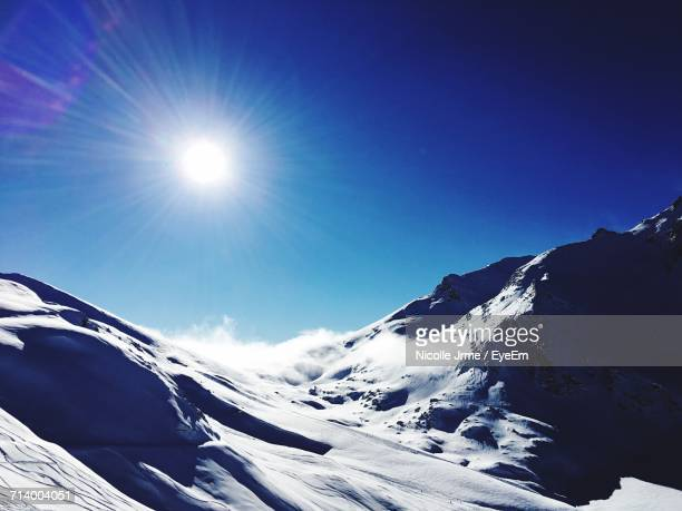 low angle view of snowcapped mountains against sky - 冠雪 ストックフォトと画像