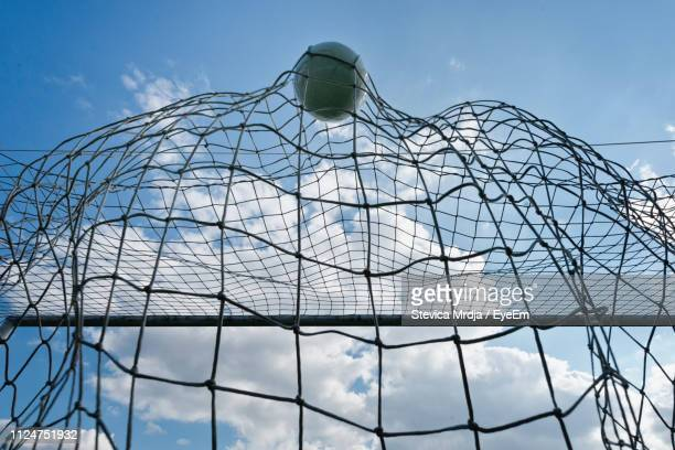 low angle view of soccer ball in goal post - ゴールポスト ストックフォトと画像