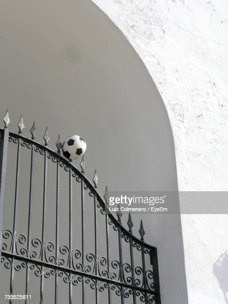 Low Angle View Of Soccer Ball On Gate Against Wall