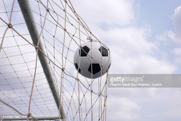 low angle view of soccer ball on net against sky - goal sports equipment stock pictures, royalty-free photos & images