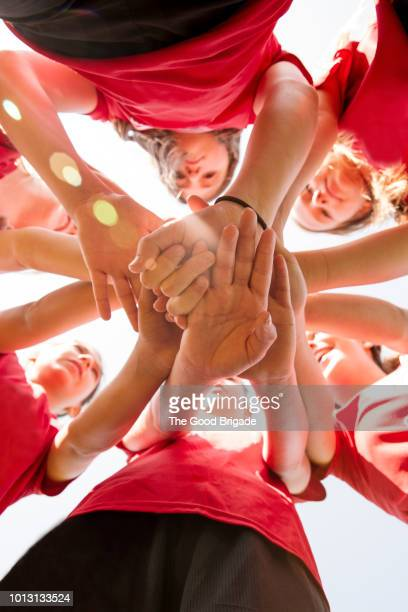Low angle view of soccer players touching hands in huddle