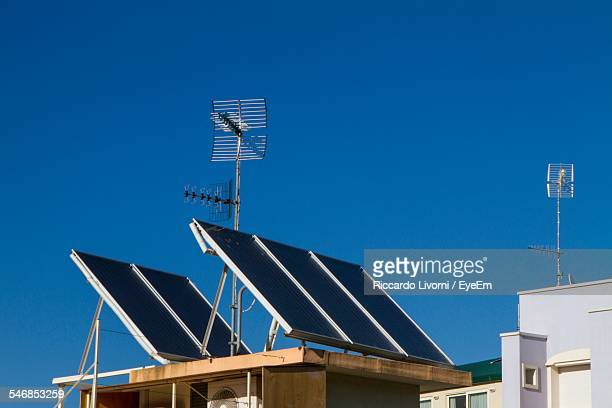 Low Angle View Of Solar Panels On House Roof Against Clear Blue Sky