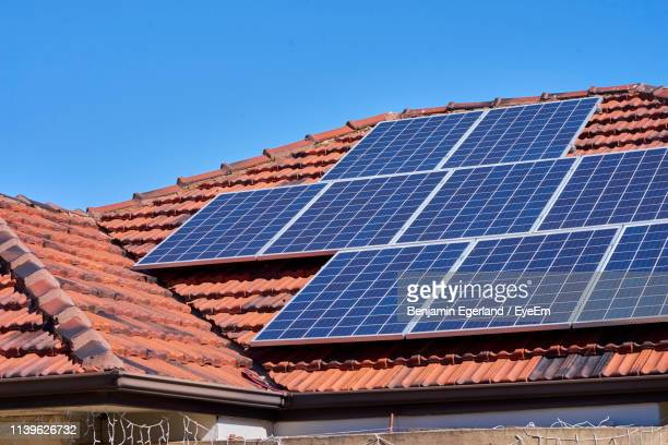 low angle view of solar panels on house roof against clear sky - solar energy stock pictures, royalty-free photos & images