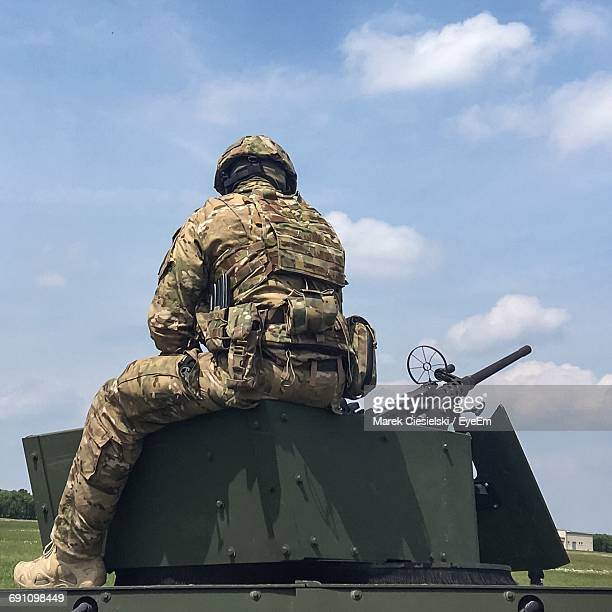 Low Angle View Of Soldier Sitting On A Tank