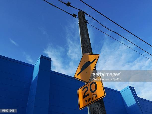 Low Angle View Of Speed Bump Sign On Wooden Post By Blue Building Against Sky