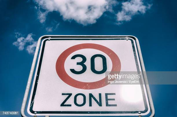 Low Angle View Of Speed Limit Sign Against Blue Sky During Sunny Day