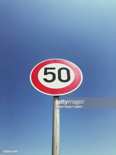low angle view of speed limit sign against clear blue sky - number 50 stock pictures, royalty-free photos & images