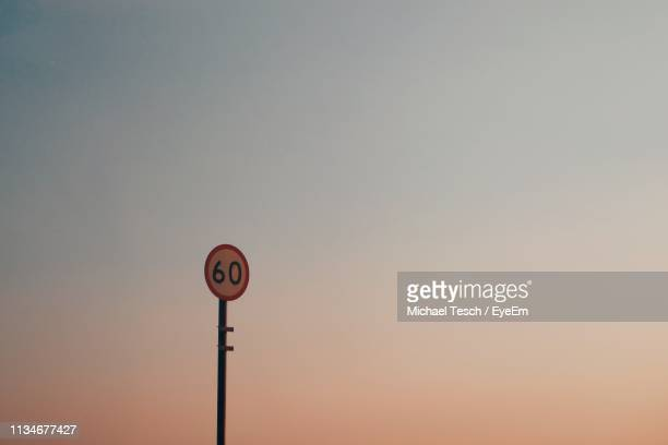 low angle view of speed limit sign against clear sky during sunset - number 60 stock photos and pictures
