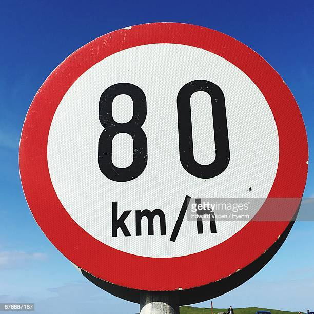 low angle view of speed limit sign against sky - speed limit sign stock photos and pictures