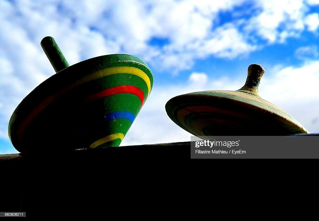 Low Angle View Of Spinning Top Against Cloudy Sky : Stock Photo