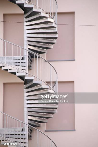 low angle view of spiral staircase against building - sabine kriesch stock-fotos und bilder